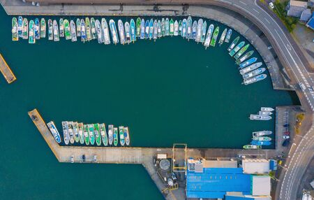 Aerial view of sail boats in marina port in harbor with blue turquoise seawater in urban city or town, Japan in travel trip and transportation concept. Top view.
