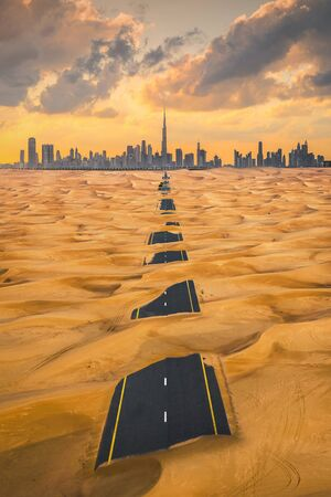 Aerial view of Dubai Downtown skyline with half desert sand road, United Arab Emirates or UAE. Financial district and business area in smart urban city. Skyscraper and high-rise buildings at sunset. 스톡 콘텐츠