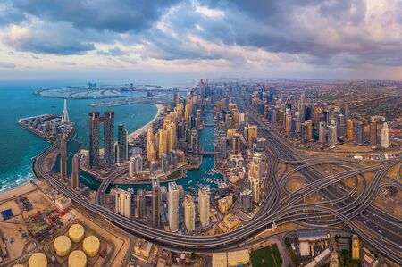 Aerial view of Dubai Marina and highways, Downtown skyline, United Arab Emirates or UAE. Financial district and business area in smart urban city. Skyscraper and high-rise buildings at sunset.