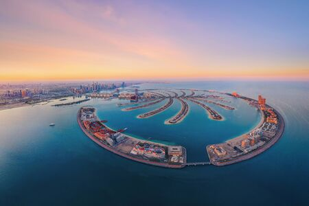 Aerial view of The Palm Jumeirah Island, Dubai Downtown skyline, United Arab Emirates or UAE. Financial district and business area in smart urban city. Skyscraper and high-rise buildings at sunset.
