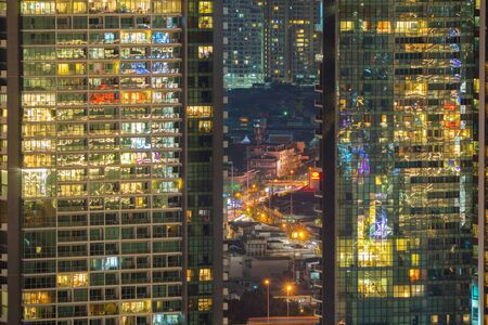 Pattern of office buildings windows illuminated at night. Lighting with Glass architecture facade design with reflection in urban city, Downtown Singapore City in financial district. 스톡 콘텐츠