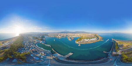 360 panorama by 180 degrees angle seamless panorama of aerial view of Mountain Fuji near industrial area, factory, Japanese port and harbour in Shizuoka City at sunset, Japan. Natural landscape. 写真素材