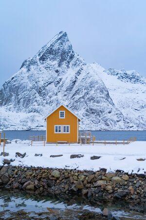 Home, cabin or house, Norwegian fishing village in Reine City, Lofoten islands, Nordland county, Norway, Europe. White snowy mountain hills, nature landscape background in winter season.