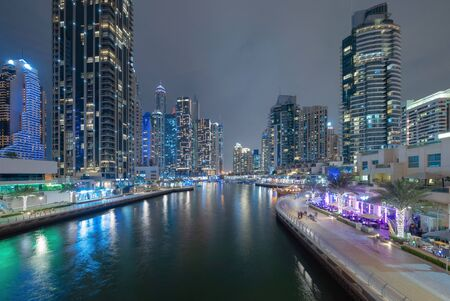 Dubai Marina and lake or river, Downtown skyline, United Arab Emirates or UAE. Financial district and business area in smart urban city. Skyscraper and high-rise buildings at night. Architecture.