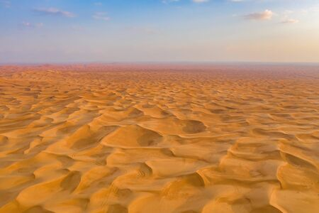 Aerial view of red Desert Safari with sand dune in Dubai City, United Arab Emirates or UAE. Natural landscape background at sunset time. Famous tourist attraction. Pattern texture of sand. Top view.