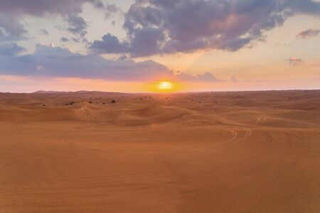 Red Desert Safari with sand dune in Dubai City, United Arab Emirates or UAE. Natural landscape background at sunset time. Famous tourist attraction. Pattern texture of sand with blue sky.