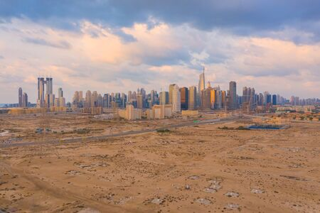 Aerial view of Dubai Downtown skyline, highway roads or street in United Arab Emirates or UAE. Financial district and business area in smart urban city. Skyscraper and high-rise buildings at sunset.