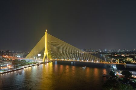 Aerial view of Rama 8 Bridge and Chao Phraya River in structure of suspension architecture concept, Urban city, Bangkok skyline. Downtown area at night, Thailand.