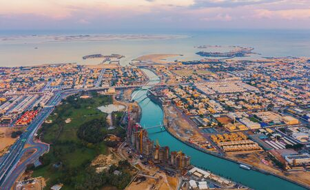 Aerial view of Tolerance bridge. Structure of architecture with lake or river, Dubai Downtown skyline, United Arab Emirates or UAE. Financial district and business area in urban city.