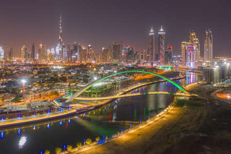 Aerial view of Tolerance bridge and Dubai downtown skyline. Structure of architecture with lake or river, United Arab Emirates or UAE. Financial district and business area in urban city at night.