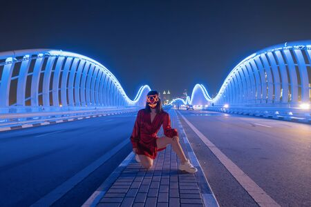 Woman with lighting neon glow mask on Meydan Bridge and street road or path way on highway in Dubai Downtown at night, urban city at night. UAE. Halloween and horror concept.