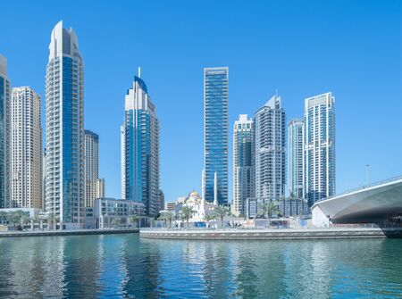 Dubai Marina and lake or river, Downtown skyline, United Arab Emirates or UAE. Financial district and business area in smart urban city. Skyscraper and high-rise buildings with blue sky. Architecture.