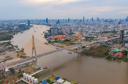 Aerial view of Bhumibol Bridge and Chao Phraya River in structure of suspension architecture concept, Urban city, Bangkok. Downtown area at sunset, Thailand.