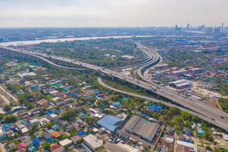 Aerial view of highway street roads and river in Bangkok Downtown skyline, Thailand. Financial business district and residential area in smart urban city. Skyscraper and high-rise buildings.