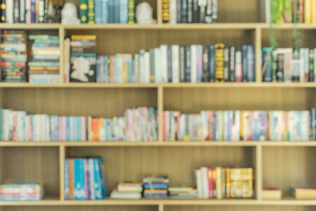 Bokeh blurry background of many book shelves library room in school or college. Abstract background for education concept.