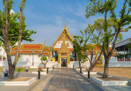 Wat Rakhang Khositaram, a Buddhist temple stupa at noon with blue sky in Bangkok city, Thailand. Thai architecture buildings background in travel trip and holidays vacation concept.