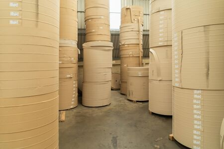Stack of a bunch of paper tube cores, tissues, in industry manufacturing plant factory. Raw product material of brown paper rolls. Cardboard cylinder cargo pattern in stock workshop storage warehouse. Reklamní fotografie
