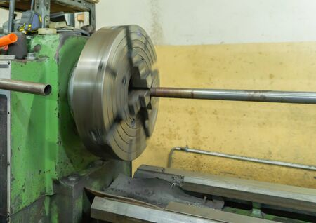 Metal fiber is rotating around big drill of steel metal lathe machine engine, technology manufacturer in operation process in industry manufacturing plant factory. Raw product equipment in warehouse.