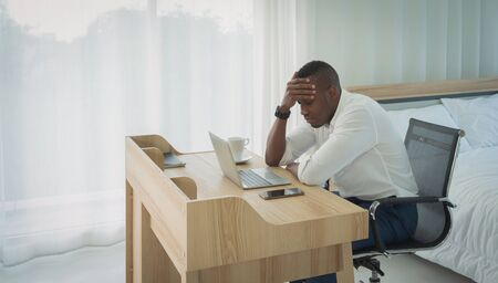 Business black american man, African person working from home, thinking about problem with computer notebook laptop and suffering from depression in quarantine in corona virus pandemic concept. Фото со стока