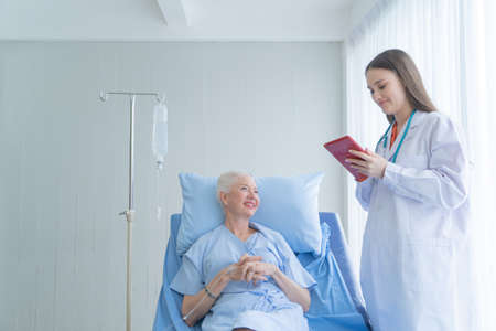Happy woman doctor talking and using tablet to sick old female senior elderly patient lying in bed in hospital ward room in medical, technology and healthcare treatment concept. Caucasian people. Reklamní fotografie
