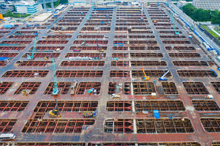 Aerial view of busy industrial under construction site workers working with cranes and excavators. Top view of precast concrete slap floor full of steel. Development high rise architecture building. Reklamní fotografie
