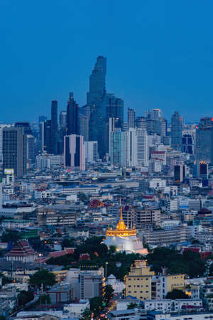 Aerial view of The Golden Mount or Wat Saket and skyscraper high rise buildings at night, Bangkok. Urban town, Thailand. Downtown City. Buddhist temples.