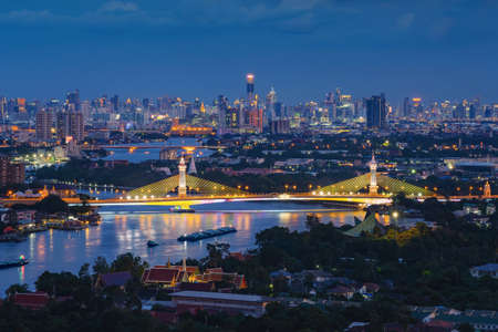 Aerial view of Maha Chesadabodindranusorn Bridge or Nonthaburi Bridge crossing Chao Phraya River and Bangkok skyline, Thailand. Urban city and downtown with skyscraper buildings at night