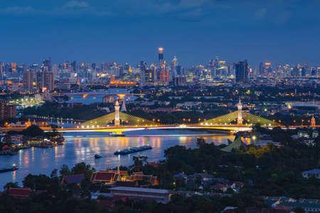 Aerial view of Maha Chesadabodindranusorn Bridge or Nonthaburi Bridge crossing Chao Phraya River and Bangkok skyline, Thailand. Urban city and downtown with skyscraper buildings at night Imagens