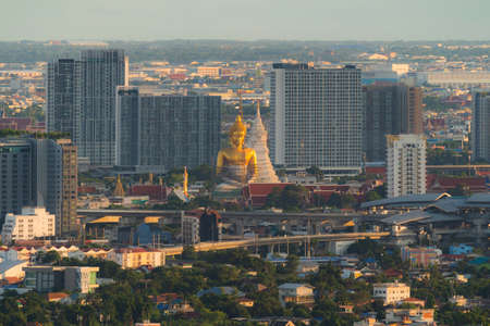 Aerial view of the Giant Golden Buddha in Wat Paknam Phasi Charoen Temple in Phasi Charoen district on Chao Phraya River at sunset, Bangkok. Urban town, Thailand. Downtown City.