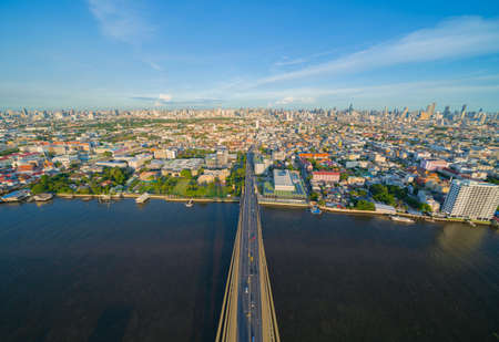 Aerial view of top of Rama 8 Bridge and Chao Phraya River in structure of suspension architecture concept, Urban city, Bangkok skyline. Downtown area, Thailand.
