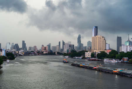 Taksin Bridge with Chao Phraya River, Bangkok Downtown. Thailand. Financial district and business centers in smart urban city. Skyscraper and high-rise buildings with storm rain. Reklamní fotografie