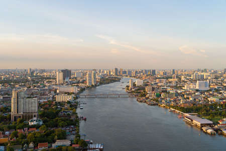 Aerial view of a bridge with Chao Phraya River, Bangkok Downtown. Thailand. Financial district and business centers in smart urban city. Skyscraper and high-rise buildings at sunset.