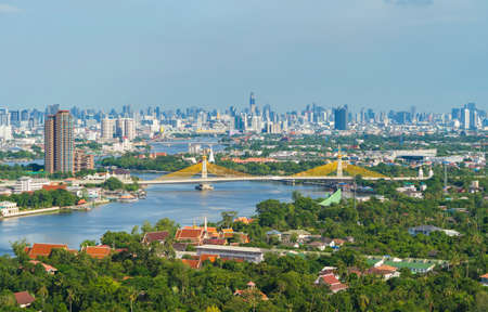 Aerial view of Maha Chesadabodindranusorn Bridge or Nonthaburi Bridge crossing Chao Phraya River and Bangkok skyline, Thailand. Urban city and downtown with skyscraper buildings.