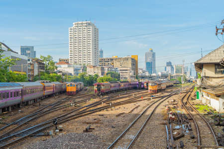 Thai local old classic train or tram on railway in Hua Lamphong terminal station with skyscraper high rise buildings in urban city, Bangkok town, Thailand in public transportation concept.
