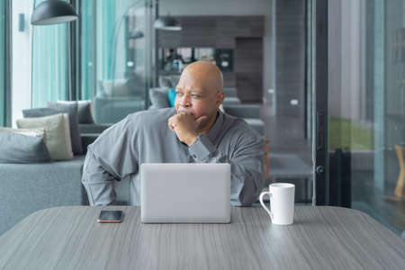 Business elderly black american man, African person working from home, thinking about problem with computer notebook laptop and suffering from depression in quarantine in corona virus pandemic concept