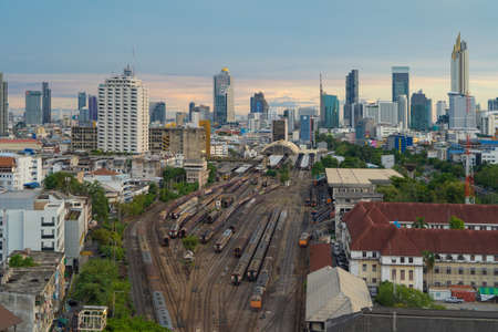 Aerial view of Thai local old classic train or tram on railway in Hua Lamphong terminal station with skyscraper buildings in urban city, Bangkok town, Thailand in public transportation concept.