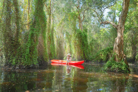 Asian woman, a tourist, reading a book on a boat, canoe or kayak with trees in Rayong Botanical Garden, Old Paper Bark Forest, tropical forest in national park in Thailand. People lifestyle activity.