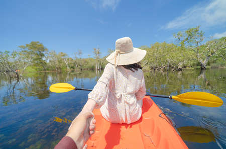 Asian woman holding her boyfriend hand, a tourist, paddling a boat, canoe or kayak with trees in Rayong Botanical Garden, Tropical Forest in Thailand. People lifestyle adventure activity recreation.