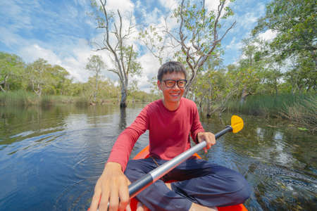 Asian man, a tourist, paddling a boat, canoe or kayak with trees in Rayong Botanical Garden, Paper Bark Tropical Forest in national park in Thailand. People lifestyle adventure activity recreation. Banque d'images