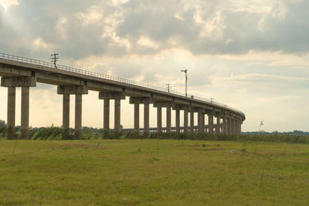 Thai local train on railway bridge at Pa Sak Jolasid Dam, the biggest reservoir in central Thailand, in Lopburi province with cloudy sky in transportation and travel concept.