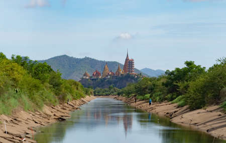 Big Golden Buddha Statue and pagoda in Tiger Cave Temple or Wat Tham Suea in Kanchanaburi province, Thailand. Famous tourist attraction landmark with river, lake, and reflection in travel trip concept Banco de Imagens - 157811768