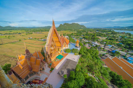 Big Golden Buddha Statue and pagoda in Tiger Cave Temple or Wat Tham Suea in Kanchanaburi province, Thailand. Famous tourist attraction landmark in travel trip concept. Banco de Imagens - 157811813