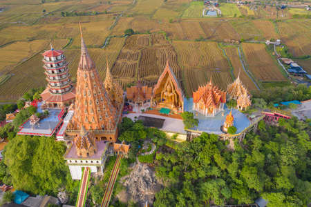 Aerial view of Big Golden Buddha Statue and pagoda in Tiger Cave Temple or Wat Tham Suea in Kanchanaburi province, Thailand. Famous tourist attraction landmark in travel trip concept.