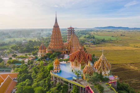 Aerial view of Big Golden Buddha Statue and pagoda in Tiger Cave Temple or Wat Tham Suea in Kanchanaburi province, Thailand. Famous tourist attraction landmark in travel trip concept. Banco de Imagens - 157812067