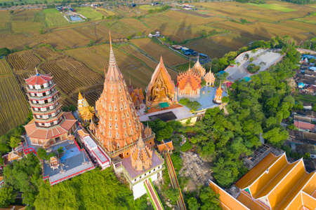 Aerial view of Big Golden Buddha Statue and pagoda in Tiger Cave Temple or Wat Tham Suea in Kanchanaburi province, Thailand. Famous tourist attraction landmark in travel trip concept. Banco de Imagens - 157812148