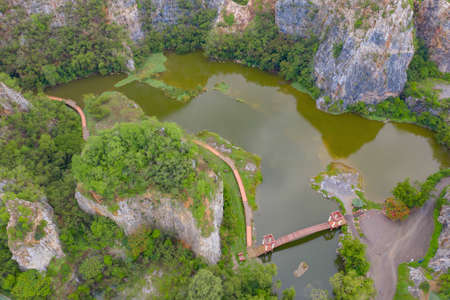 Aerial view of Khao Ngu Stone. National park with river lake, mountain valley hills, and tropical green forest trees at sunset in Ratchaburi, Thailand in travel trip. Natural landscape background. Banco de Imagens - 157812232