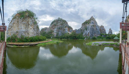 Khao Ngu Stone. National park with reflection of river lake, mountain valley hills, and tropical green forest trees at sunset in Ratchaburi, Thailand in travel trip. Natural landscape background. Banco de Imagens - 157812241