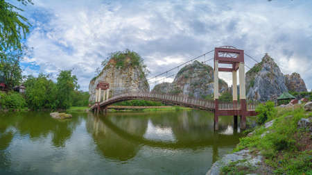 Khao Ngu Stone. National park with reflection of river lake, mountain valley hills, and tropical green forest trees at sunset in Ratchaburi, Thailand in travel trip. Natural landscape background. Banco de Imagens - 157812242