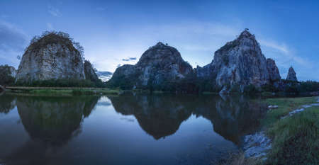 Khao Ngu Stone. National park with reflection of river lake, mountain valley hills, and tropical green forest trees at sunset in Ratchaburi, Thailand in travel trip. Natural landscape background.