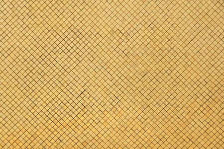 Golden or gold art grid square mosaic tiles wall pattern surface texture. Close-up of architecture interior shinny material for design decoration background. Thai style Reklamní fotografie